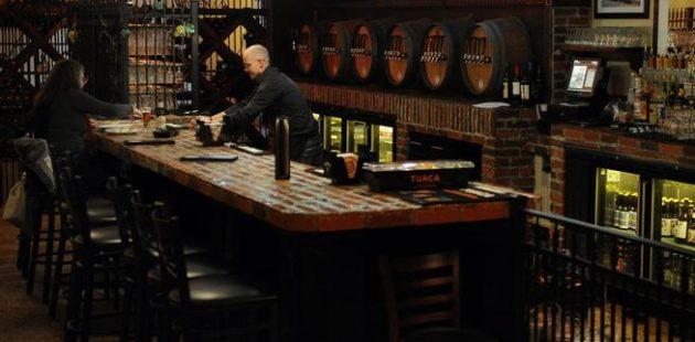 WHEAT RIDGE, CO - DECEMBER 4: Zac Gaume, nephew to owner Bill Gaume, serves a customer at Iron Rail Tavern on December 4, 2014, in Wheat Ridge, Colorado. Bill Gaume opened Iron Rail Tavern in October. (Photo by Anya Semenoff/The Denver Post)
